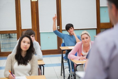 Student raising hand to ask question in college classroom Stock Photo - 16065681