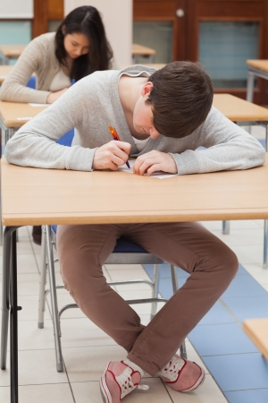 Student writing at desk in classroom photo