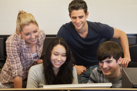 educational institution: Students sitting standing and smiling at computer in college