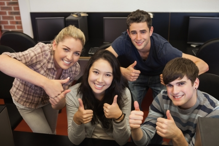 Students giving while thumbs up in college computer room Stock Photo - 16078393