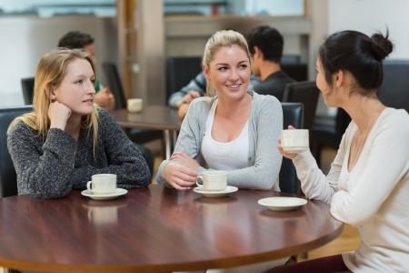 drinking coffee: Los estudiantes que hablan juntos en la tienda de la universidad caf� y sonriente Foto de archivo