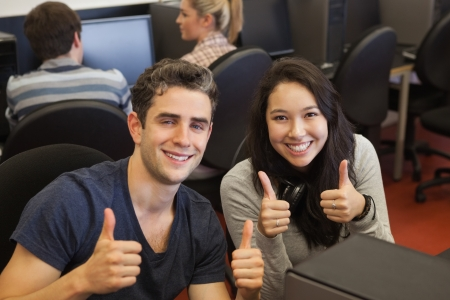 college class: Happy students giving thumbs up in computer class