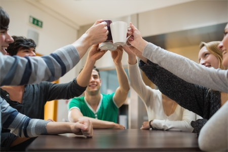 Students sitting around the table clinking mugs in college cafe photo