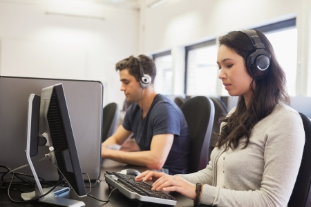 Students working in computer class wearing headphones in college Stock Photo - 16066424