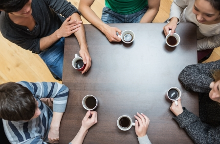 student desk: Students sitting around table drinking coffee in college cafe