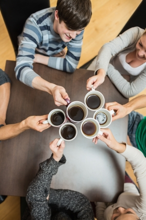 friends coffee: Students sitting holding cups of coffee smiling in college cafe Stock Photo