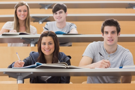 adults learning: Students sitting at the desk while smiling at the lecture hall