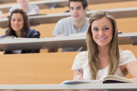 Studenten zitten in de collegezaal terwijl glimlachend en het maken van notities