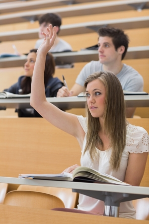 Woman sitting at the lecture hall with hand up to ask question photo