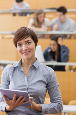 institution: Woman standing holding a tablet computer smiling at the lecture hall