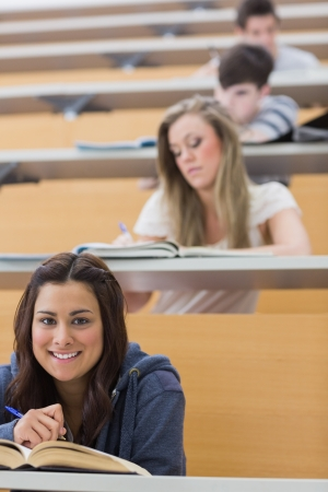 Student sitting reading a book while smiling in lecture hall photo