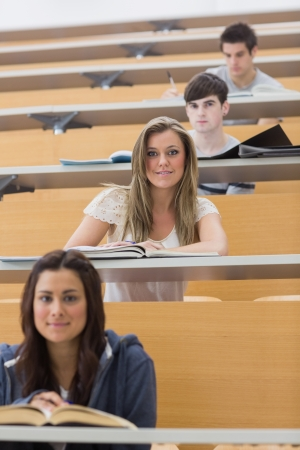 Students sitting while smiling in lecture hall in different rows photo