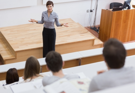 Leraar staande te praten met de studenten van de collegezaal Stockfoto