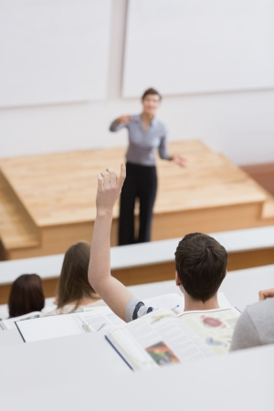 lecturing hall: Teacher standing explaining while student hands up Stock Photo