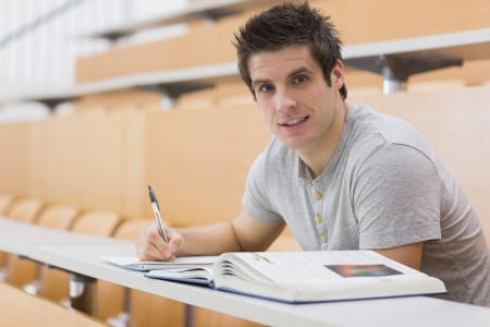student desk: Student sitting at the desk while smiling in lecture hall