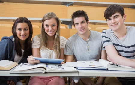educational institution: Students sitting at the lecture hall smiling with tablet pc