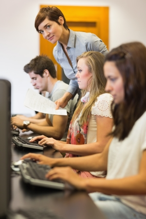 Students sitting at the computer while teacher is looking on in college computer class Stock Photo - 16058473