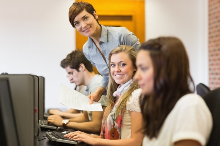 Student and teacher smiling at the computer room of the university Stock Photo - 16055803