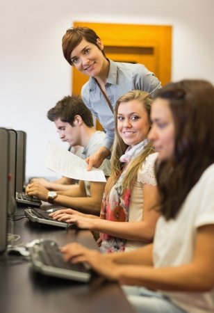 Students sitting at the computer while teacher smiling in college Stock Photo - 16057713