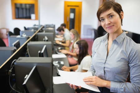 Teacher standing at the computer room holding papers in college Stock Photo - 16068814