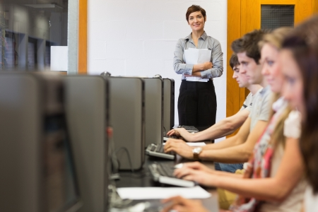 Teacher standing while students sitting at the computer room in college photo