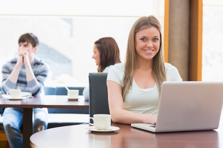 Girl sitting at the coffee shop smiling with laptop in college photo