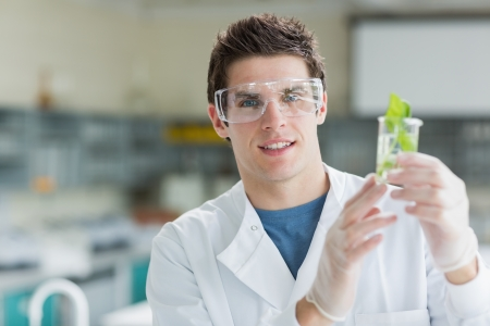 Student standing at the laboratory smiling and holding beaker with seedling photo