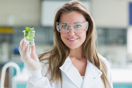 lab coat: Student standing at the laboratory while smiling and holding plant in a beaker