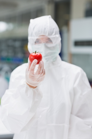 Woman standing at the laboratory holding a tomato wearing protective suit photo