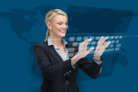 Businesswoman standing while typing on projected keyboard on world map background photo