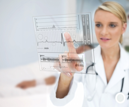 health service: Doctor using ECG interface hologram and smiling Stock Photo