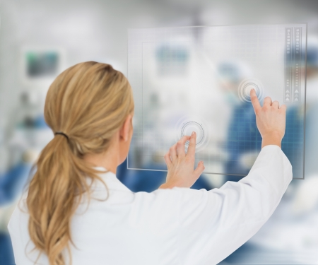 Doctor standing at the surgery with digital interface hologram Stock Photo - 18684440