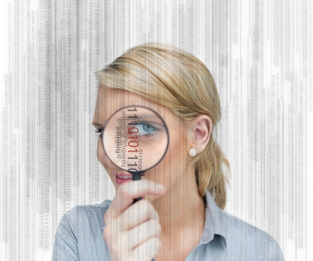 Woman standing while holding a magnifying glass photo