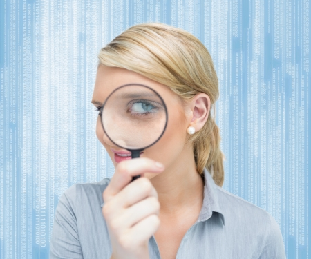 Blonde woman looking through magnifying glass photo
