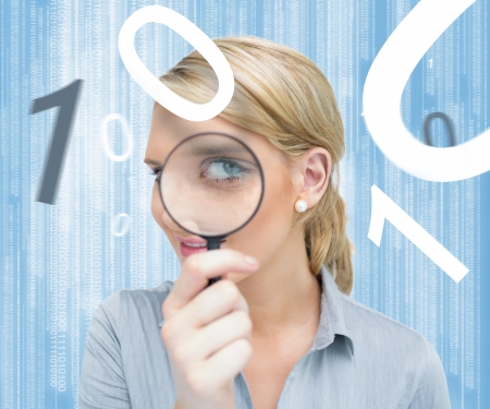 Woman looking through magnifying glass on digital bakcground with numbers photo