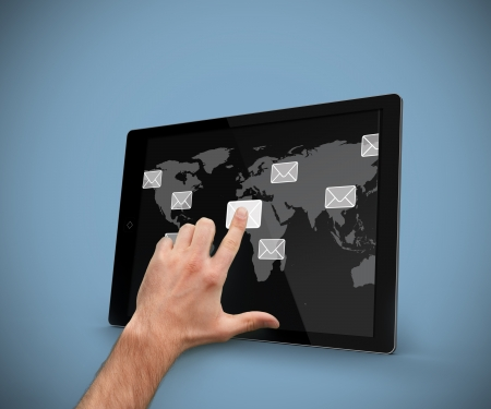 Hand pointing at tablet computer with email symbols and world map backdrop against blue background photo