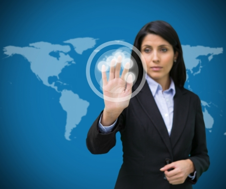 international internet: Businesswoman standing touching holographic screen against blue world map background