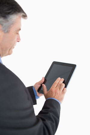 Businessman scrolling through his tablet pc photo