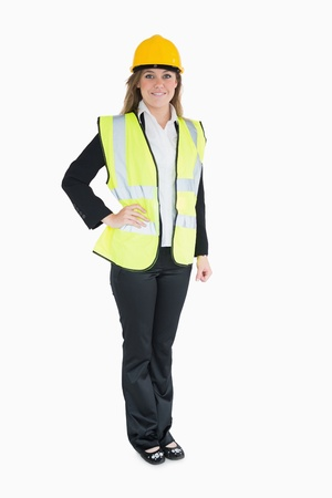 out of context: Woman in a suit wearing high visibility vest and hard hat Stock Photo
