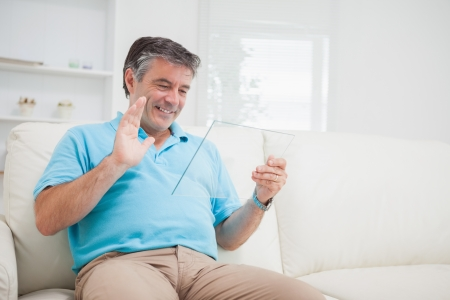 Smiling man using video chat waving at clear pane as digital tablet pc photo