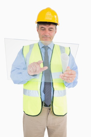 Man in vest and with helmet holding pane and pressing as a digital tablet while smiling photo