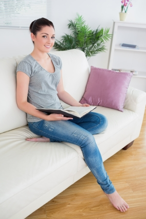 Young woman sitting in a living room on the couch and holding a book while smiling photo