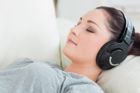 woman couch: Woman lying on the couch in a living room and listening to music with headphones