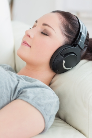 Relaxing woman lying on the couch in a living room and listening to music photo