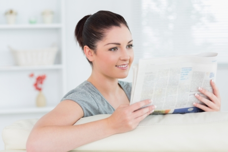 Smiling woman sitting on the ouch in a living room and reading newspaper photo