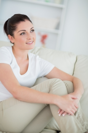 Thinking woman sitting on the couch in the living room and smiling Stock Photo