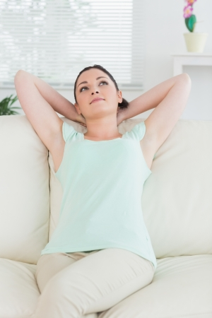Relaxing woman sitting on a couch in a living room and being thoughtful photo