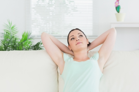 Woman sitting on a couch in a living room and relaxing photo