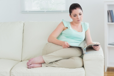 Woman relaxing on sofa with magazine in living room Stock Photo - 16053557