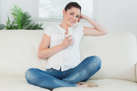 Smiling woman sitting on the couch in a living room and holding a cup of coffee photo